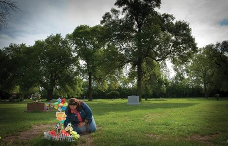 Five-year-old Christopher Valdez was killed by his mother's boyfriend on Nov. 25, about two months after the Illinois Department of Children and Family Services closed his child abuse case. His aunt, Katrina Valdez, visits his grave. Photo by Joe Gallo.