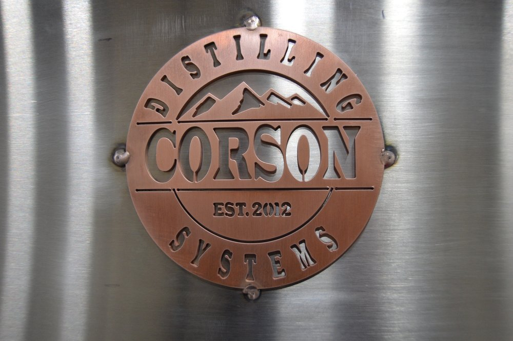 corson distilling equipment logo copper badge