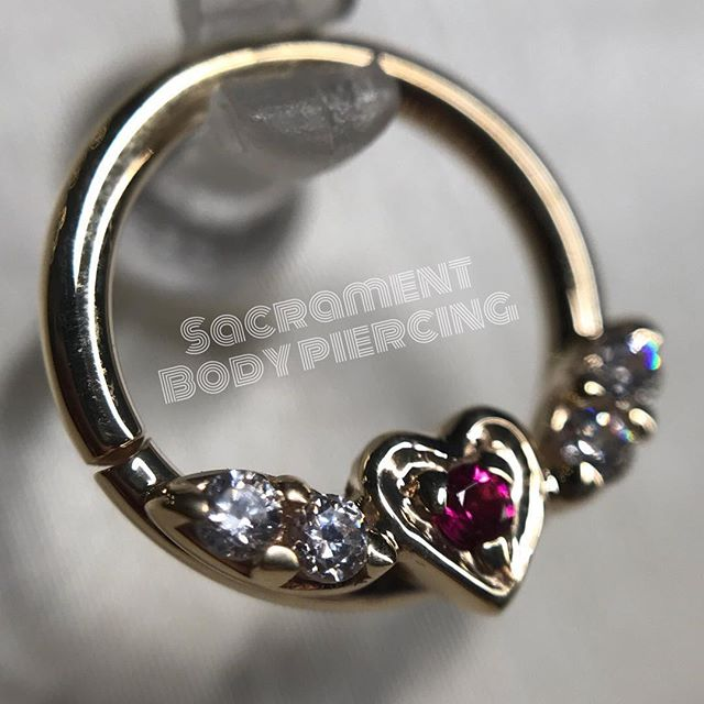 "Beautiful jewelry piece available from @sacramentbodypiercing 🙌🏼 Come check em out! Tues-Sat, noon-7pm ・・・ ""Today's current favorite- the flying heart with genuine pink topaz and 4 brilliant cut CZs, all set in solid 14k yellow gold. This clicker is so hot, in stock and ready for your daith, septum or maybe even helix! Stop in and see all the new pretties in stock and are waiting for their forever homes!! Open Tuesday - Saturday 12-7"" #obsessed #pierced #piercings #bodypiercing #whitegold #topaz  #gems #fancy #legitbodyjewelry #mua #lakeforest #irvine #missionviejo #danapoint #newportbeach #costamesa #anaheim #anaheimhills #uci #saddlebackcollege #orangecounty #oc #bodyjewelry #treatyoself #lagunahills #danapoint #vaticanstudios #sacramentbodypiercing"