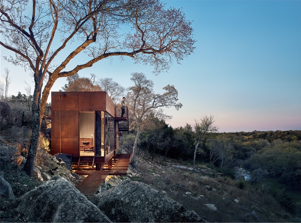 """CLEAR ROCK RANCH     2017 AIA Austin Design Award Winner    Clear Rock Lookout is a raw steel hunting blind, writing studio, and observation deck that celebrates the stunning landscape and wildlife views. The 450sf building is nestled below a limestone cliff edge, and has to be """"discovered"""" when approached from the top of the mesa. This gradual reveal of the building strengthens the unfolding landscape panorama made possible from the unique vantage provided by the structure.  The site was specifically chosen for its views by the owner after years of slowly traversing and mapping the wooded cliff edge. The modern form contrasts with the Hill Country vernacular used on the rest of the 1,000 acre West Texas ranch. Naturally weathering steel was chosen to age with the surroundings and to pay homage to the owner's youth spent welding oil tanks.  Large sheets of glass, a variety of warm woods, and a highly detailed assembly complete the """"jewelbox in the landscape"""" expression of the lookout.   Contractor:  Ron Reue Construction   Steel Fabrication :  Longhorn Welding    Structural Engineers :  Arch Consulting Engineers    Photo Credits :  Casey Dunn    Publications:   Texas Made/Texas Modern ,  Dezeen  ,  ArchDaily ,  Dwell  ,  Uncrate ,  Texas Architect Magazine ,  Austin Home Magazine"""