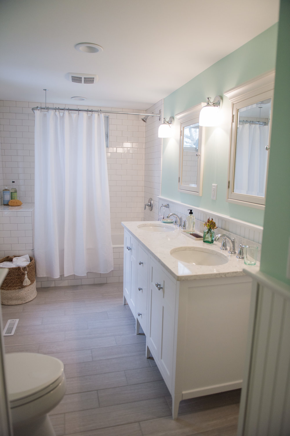 By knocking down the wall in between, our square footage doubled!  This made room for a double vanity and a soaking tub/shower combo.  A classic New England aesthetic with some modern touches was achieved through the finish and fixture selection.  And that green...so pretty and calming!
