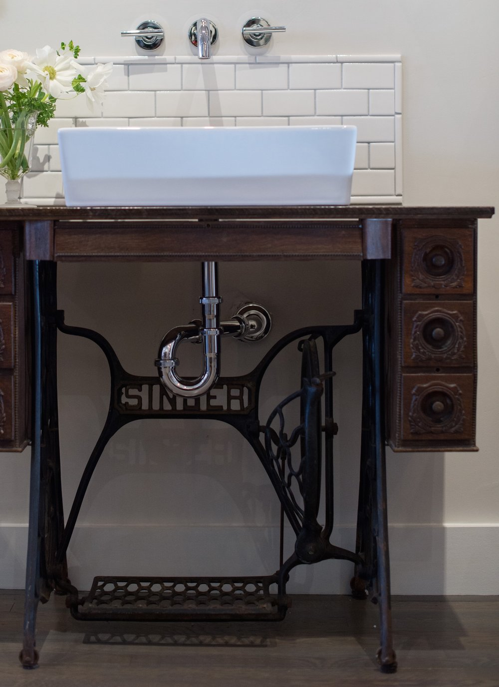 Because the original top had a cutout for the sewing machine and was in rough shape, we had it rebuilt and stained to match.  The vessel sink and wall mounted faucet adds a modern contrast to the antique details of the original drawer fronts and signature wrought iron base.