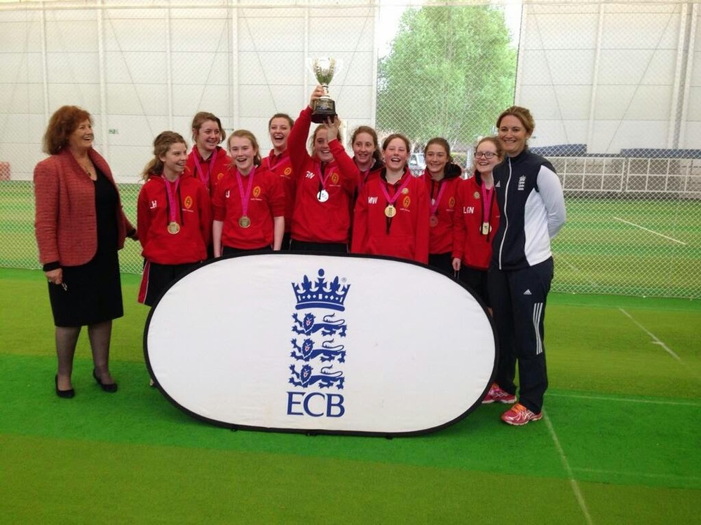 Captain Georgie Walker holds aloft the trophy as England captain Charlotte Edwards (standing at right hand side) looks on