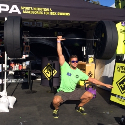 Volunteer Rob (North East Regionals Athlete) one-hand overhead squatting at one of the booths.  Impressive!