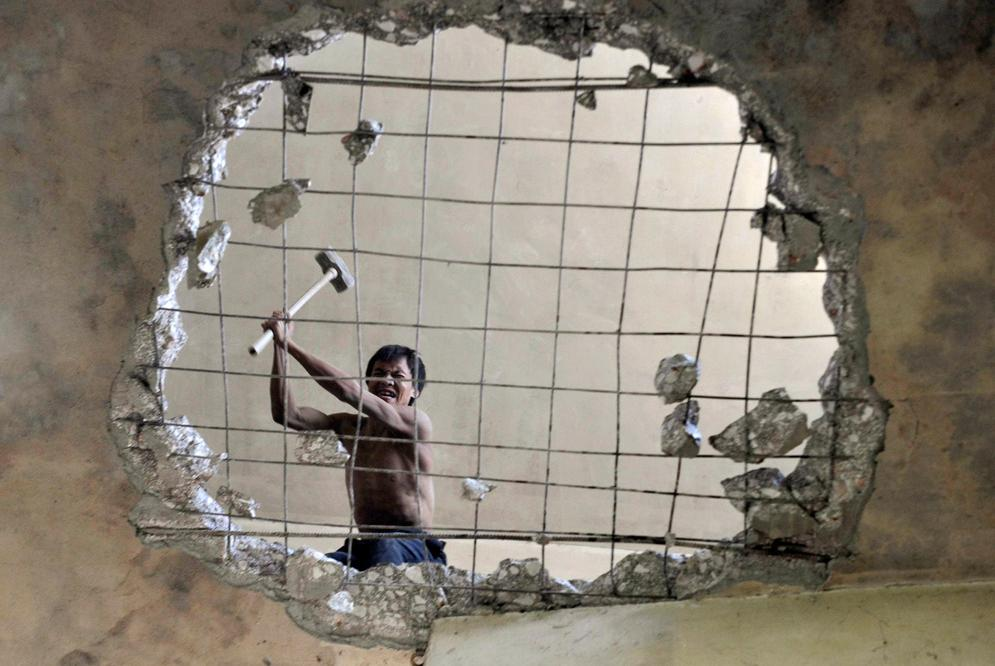 """A labourer demolishes a building"" / Reuters"