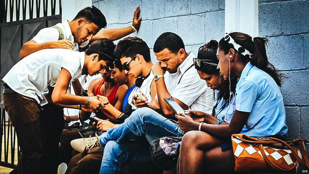 Cubanos usan sus dispositivos móviles para conectarse a internet a través de wi-fi en una calle de La Habana. Foto de Archivo EFE