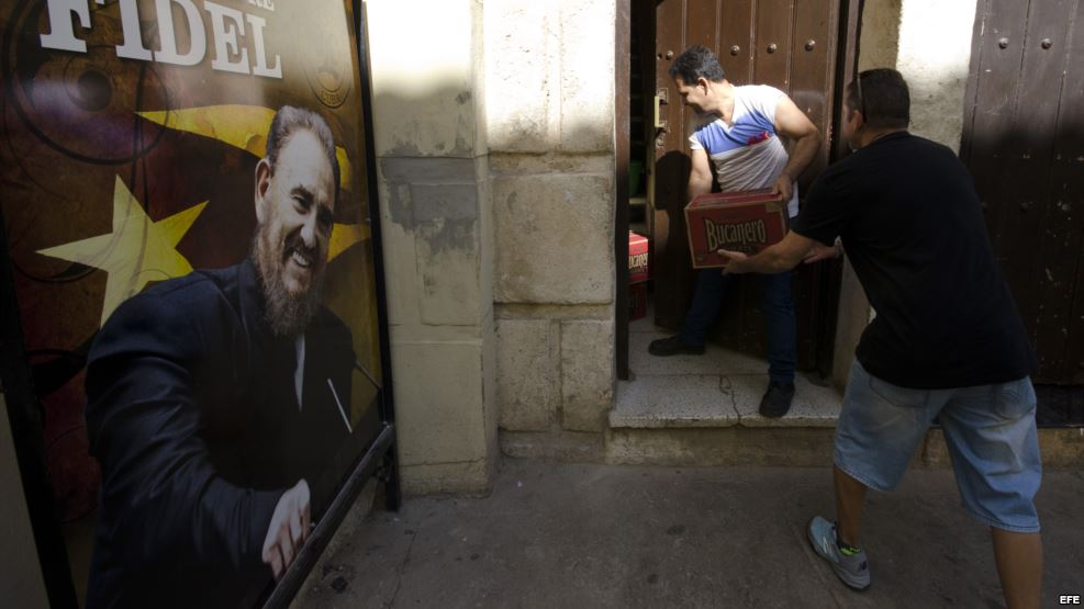 Dos hombres cargan cajas de cerveza en un restaurante privado un día después de la inhumación de las cenizas de Fidel Castro.