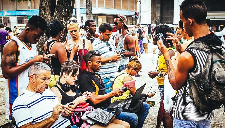 Varias personas se conectan a Internet en un parque de La Habana ante la proliferación de los puntos WiFi. EFE/ARCHIVO