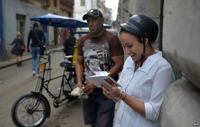 Una mujer se conecta a internet desde su celular en una calle de La Habana.