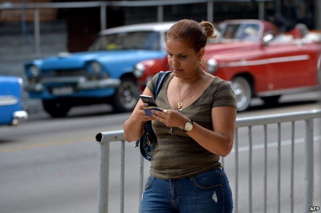Una mujer usa su teléfono para conectarse a internet en una calle de La Habana.