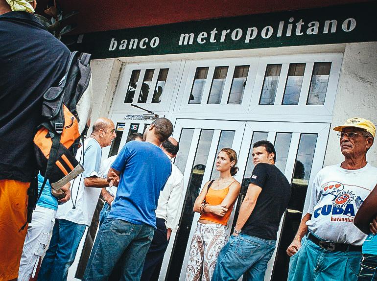 Varias personas hacen cola en las puertas de un banco de la capital cubana.EFE