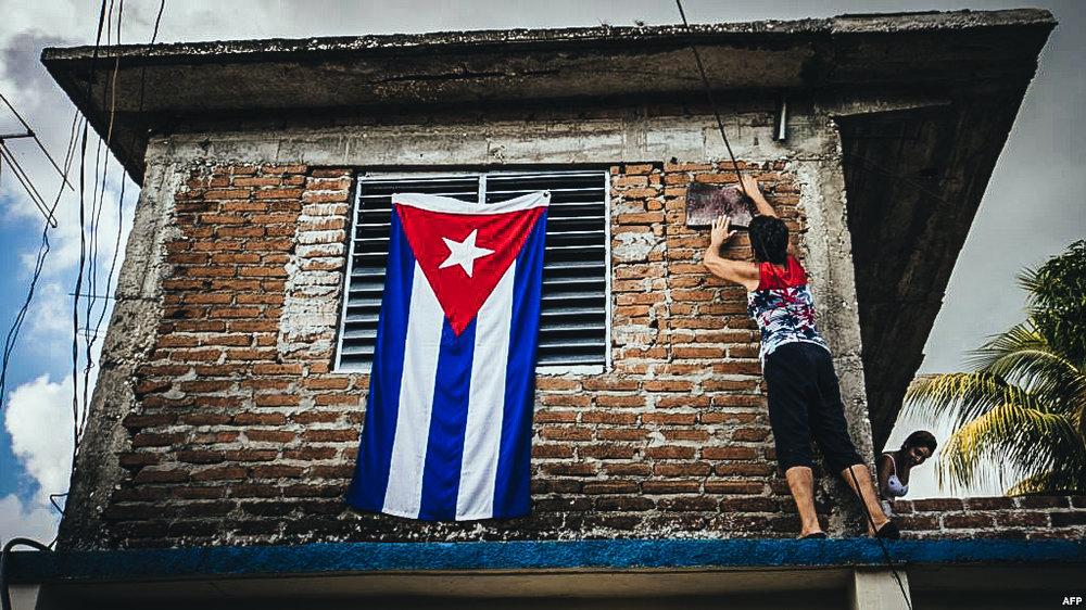 Una mujer cuelga una bandera cubana en su ventana.