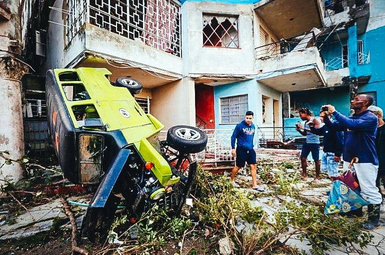Vecinos de La Habana miran un auto lanzado contra una vivienda por el tornado que azotó la capital cubana en la madrugada del 28 de enero de 2019.