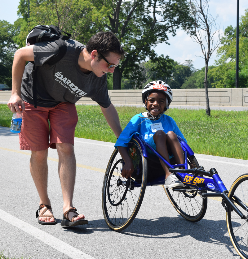 Young boy in a racing chair will volunteer at his side.