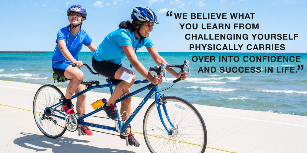 "Guide and Athlete ride a tandem bike on the bike path near Lake Michigan. ""WE BELIEVE WHAT YOU LEARN FROM CHALLENGING YOURSELF PHYSICALLY CARRIES OVER INTO CONFIDENCE AND SUCCESS IN LIFE."""