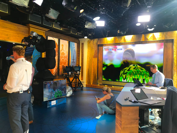 Lalas (standing, left) watches the Nigeria-Iceland match in Fox's World Cup studio with host Rob Stone (seated at the desk on the right).