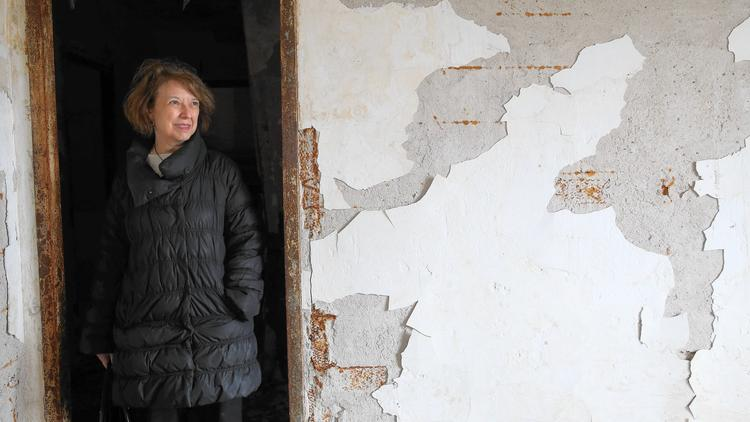 Sunny Fischer, board chairwoman of the National Public Housing Museum, stands beneath a rusty door frame in the former public housing building in the 1300 block of West Taylor Street that will house the museum. (Abel Uribe / Chicago Tribune)