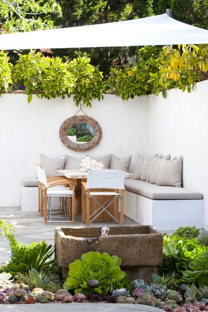 The traditional furniture in this backyard room highlights both aspects of comfort and it is fully functional.  The combination of neutral tones and the addition of the shade and water feature add a nice touch. Image as seen on houzz.com