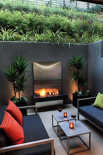 The metal accents in this backyard paired with the concrete walls really has a great industrial feel in a lush environment.  Coupled with fire and the plants, this backyard room has created a beautiful area for entertaining and is utilizing all of these eye catching elements.   Image as seen on lovelyhomedesigns.com