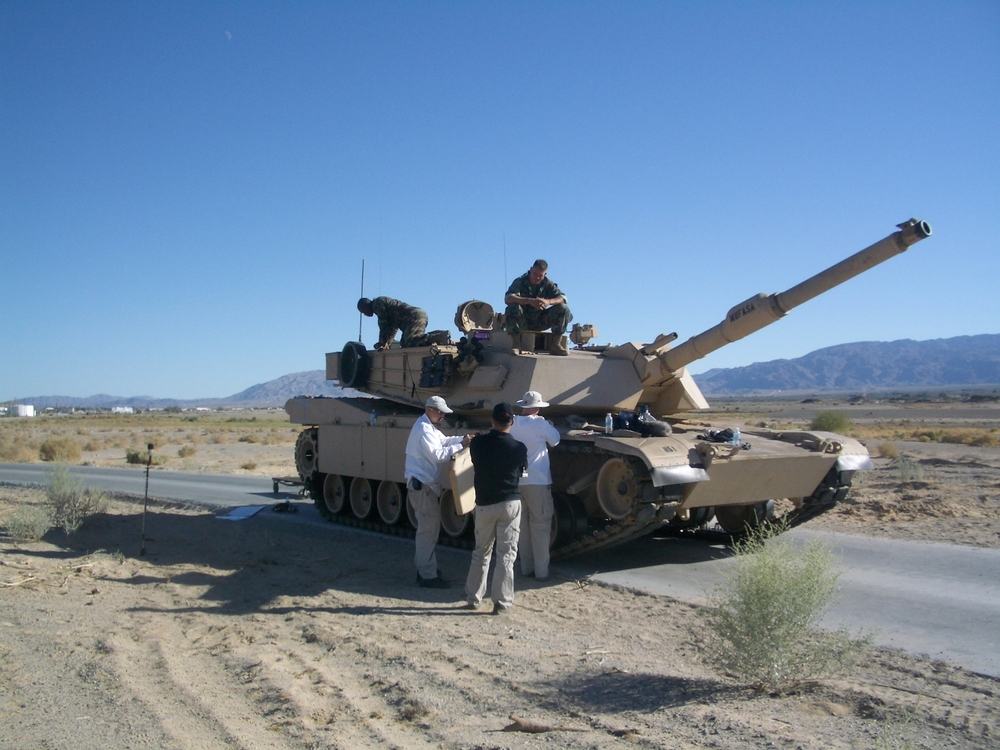 Kevin Collins, Watson Wu, & Aaron Marks rigging mics and cables to record an Abrams tank