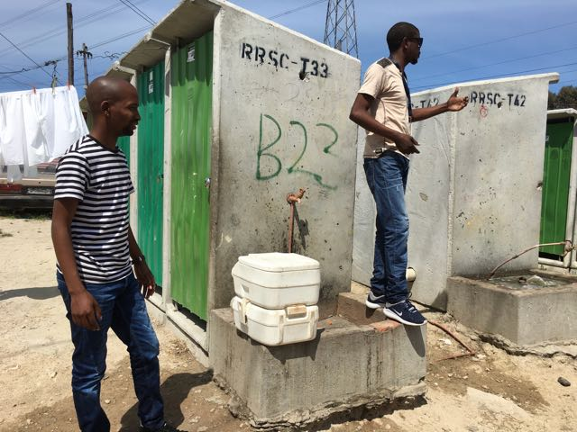 Community Activists with the Social Justice Commission explain toilet options for residents of the Khayelitsha township in Cape Town, South Africa.