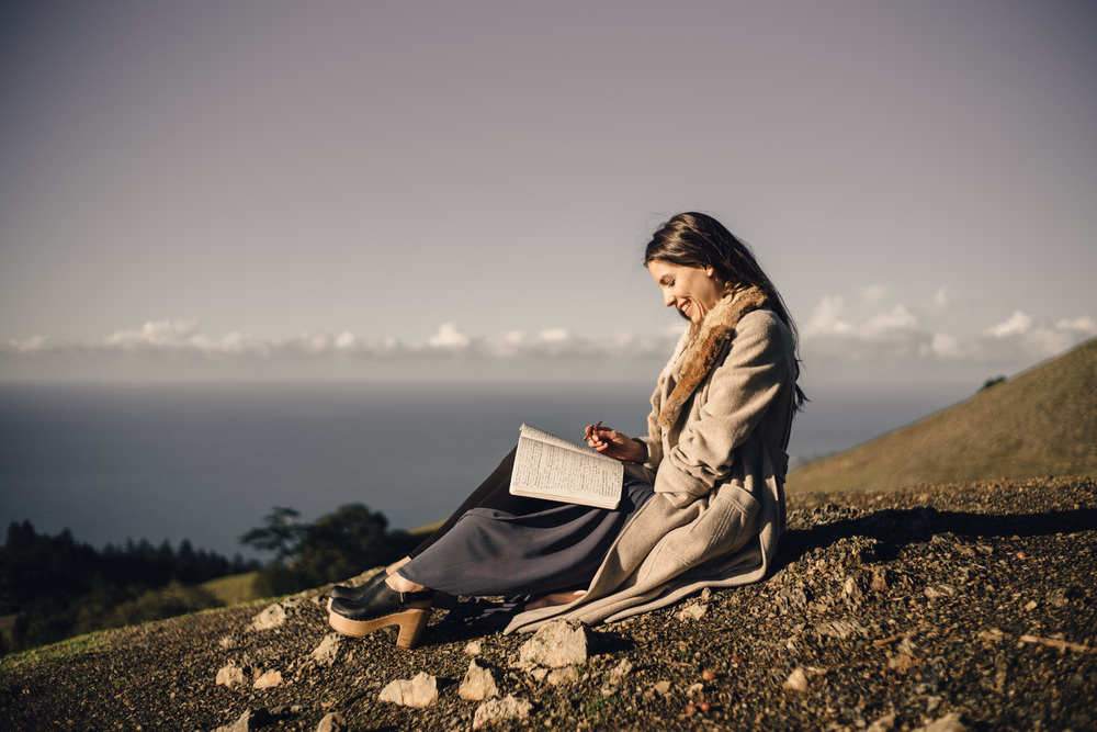 Overlooking the Pacific ocean, somewhere between rock and sky, I'm laughing and journaling. Photo by  Jaclyn Le.