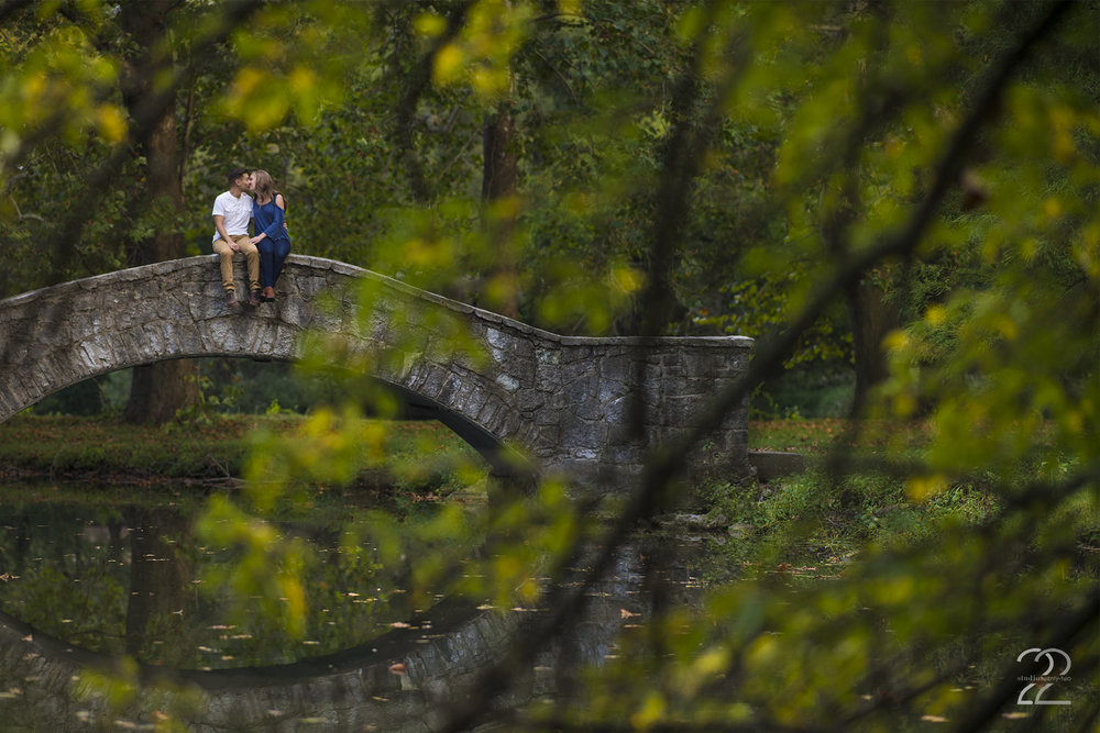 The stone arch bridges at Eastwood MetroPark are some of my favorite features at this Dayton engagement photo location, and it's easy to see why! They boast such amazing character, and with the beautiful greenery surrounding them, you can't go wrong with your engagement photos. One thing I love to do is layer my engagement photos with an interesting background, then the subject (that's you!), and finish them with and interesting foreground to give the image a 3D feel. You can see here that by crouching in the bushes and shooting through them with my Nikon 105mm f/1.4 (one of my favorite portrait lenses!), I'm able to compress the image and tell the entire story by building layers in the image. I want your engagement photos to tell the full story, and I love doing that creatively in many different ways.