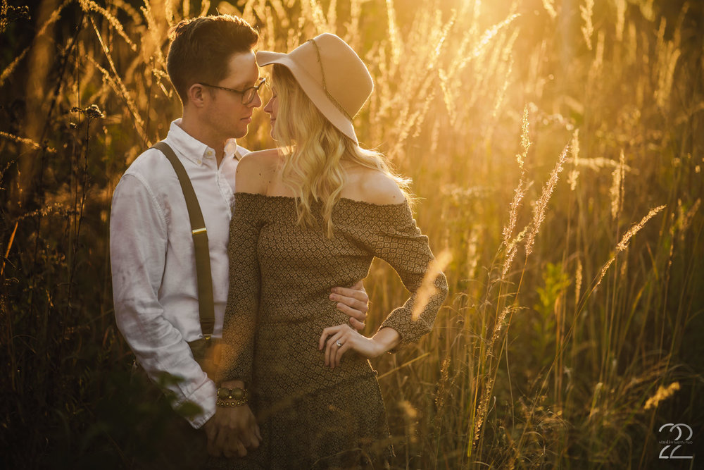 Oh, that luscious golden light at the peak of Golden Hour. It's stunning at Wegerzyn Gardens, and this image proves it! Dillon and Corrie came in their rustic attire, and it was perfect for the gold light that washed over them as the sun set low before dipping below the horizon. Corrie's beautiful bracelets perfectly accented with her hat, and she pulled off a stunning look to compliment Dillon's classic dress shirt and suspenders.