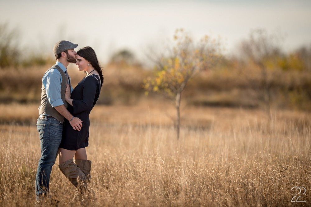 """One of the biggest questions I receive before engagement sessions is, """"What do we wear?"""" The short answer is whatever you feel is YOU...but there's always a long answer to any question, too! In this image you'll see Jake + Krysta flawlessly tie together, yet aren't matchy. I love the accent vibes that come from Jake's matching vest and hat, but that he keeps it casual with a nice pair of dark denim jeans. Krysta went with an adorable dress that flattered her body in a deep blue that complimented the browns and lighter blues in Jake's clothing, as well as the environment we'd be working in, and topped it off with a great pair of brown boots that matched Jake's clothing, and a great long necklace and earrings. Your clothing for your engagement session doesn't need to be over the top; it needs to be YOU! Working to compliment one another, as well as the location you've chosen to do your engagement photos, will allow your style to shine and tie everything together. Don't be afraid to ask your photographer for tips. I love when couples send me photos of potential outfits to make sure they're on the right page, and together we work to make sure you shine in your engagement photos!"""