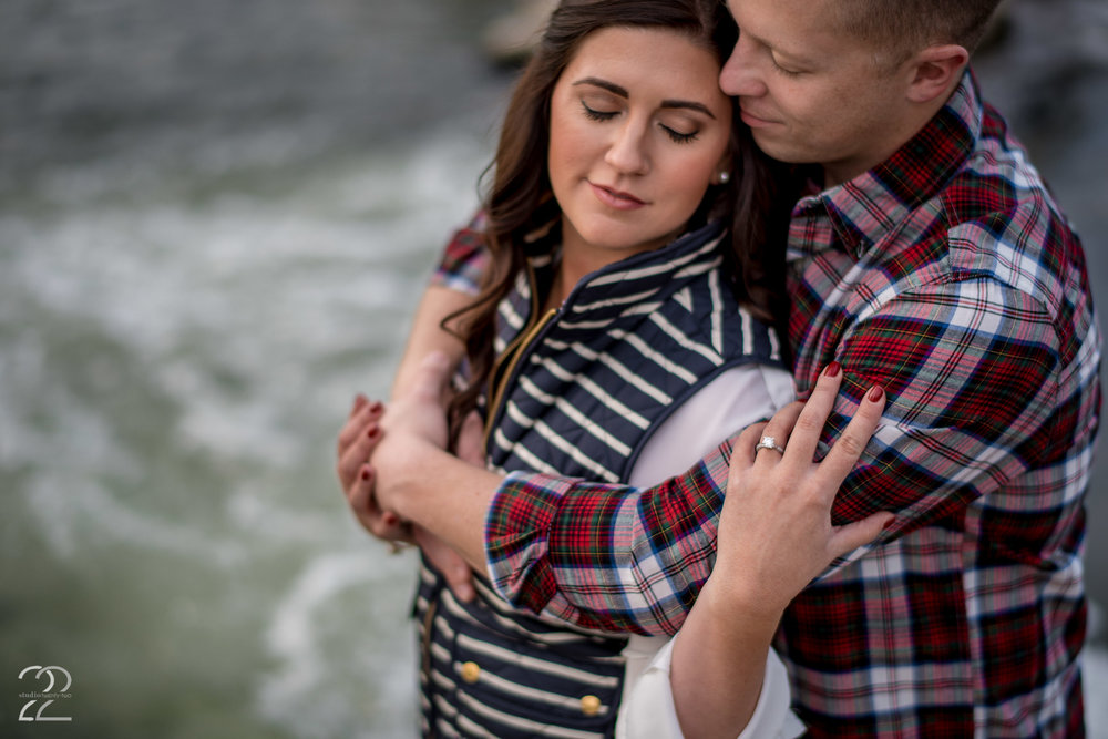 """There's a beautiful little """"waterfall"""" feature at Eastwood MetroPark as well, where on many evenings you'll see kayakers practicing their moves. The rushing water and textures from the clothing choices that Mike and Ashlea chose go perfectly hand in hand to make a great image. Their content smiles in this cozy engagement photo make it hard not to love this image, and it was made with of my favorite lenses for intimate portraits, the Nikon 58mm f/1.4. The character and depth of this lens makes for beautiful, intimate images, which is perfect for Dayton engagement photos."""