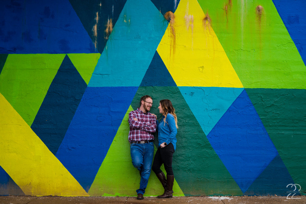 One of my favorite things to do with couples during their engagement sessions is to simply wander. When we have the opportunity to spend time just hanging out, finding new locations for engagement photos, it's always a great time. With Nick + Erica, they were game to travel all over the Dayton area, and because of this, we found these amazing, multi-colored murals that reminded me of the murals in DUMBO in Brooklyn, New York! The brightly painted walls brought cheer on an overcast winter day, and added nicely to the locations we chose for their Dayton engagement photos.  Sony A9 | Sony 70-200mm f/2.8 @ 76mm f/2.8 | ISO 100 | 1/125 sec