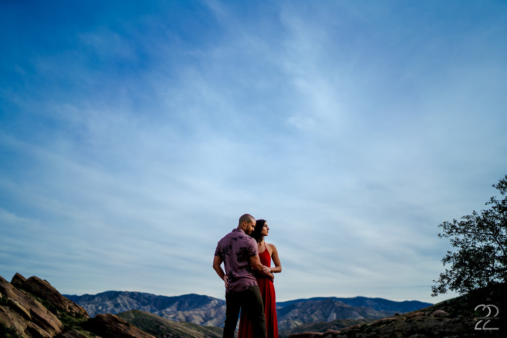 "With such beauty as the Vasquez Rocks as a backdrop for a couples, wedding, or engagement session, you cannot go wrong! High on top of a rocky mountain, Michael embraces Natalie as they look toward the sunset. Intimate environmental portraits are always some of my favorites, as it feels like you see the couple being one with nature. The West Coast is always one of my favorite places to be a wedding and engagement photographer, and this time at the Vasquez Rocks did not disappoint!   Sony A7Riii | Sony 35mm f/1.4 @ f/1.4 | ISO 50 |  1/2500 sec | DVLOP presets: Jide Assumpção's ""Rio"""