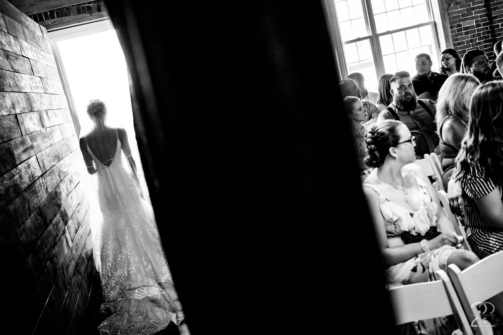 Megan loves to find ways to showcase multiple stories in one photograph. In this shot from Dillon and Corrie's wedding at Top of the Market in Dayton, Ohio you can see the guests eagerly waiting the ceremony while Corrie arrives at the venue.