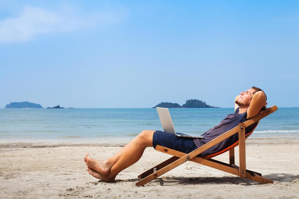 man with computer at the beach
