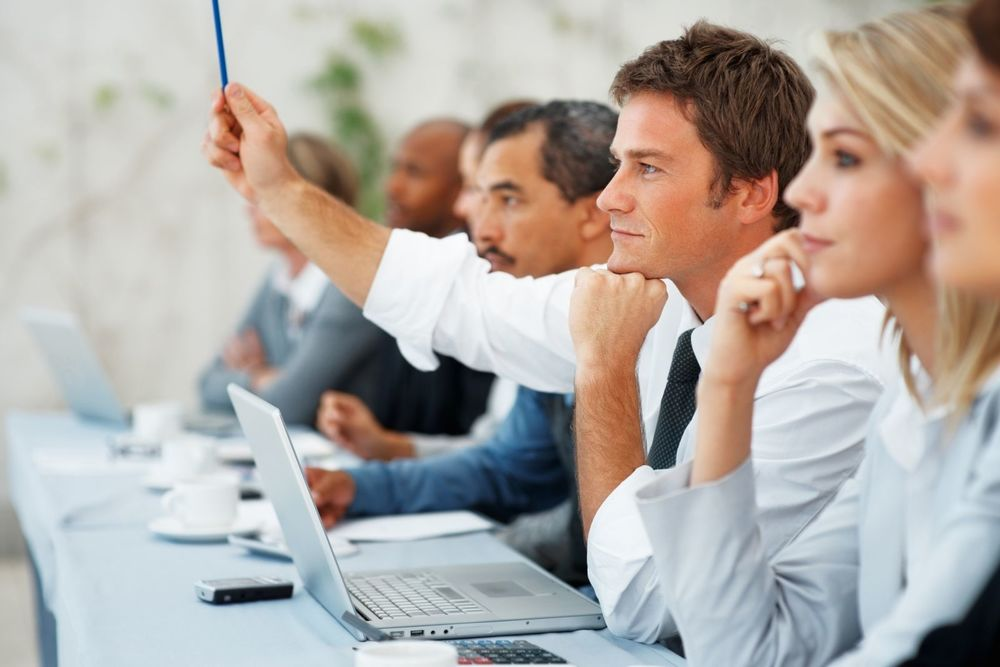 man raising hand business meeting