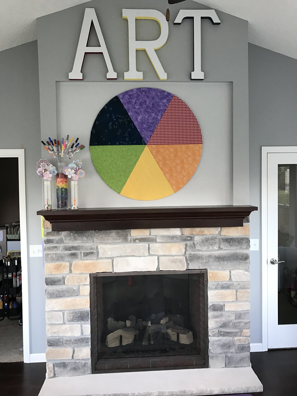 This is a double fireplace. The other side shows up in the living room. The color wheel is made using the same fabrics as the pillows. They are stapled to pie shaped wedges. I was so glad to have a math background when we figured out how to hang this. Did you notice the marker bouquet?