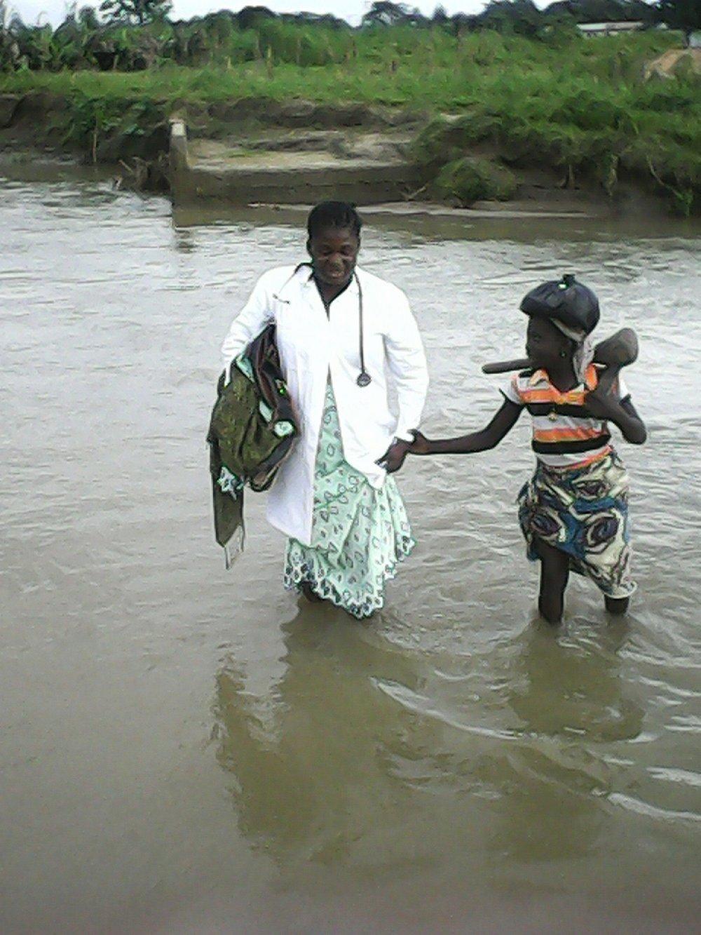 Fund for Global Health Nurse Deborah Silas bringing health care to a village in Nigeria during the rainy season.