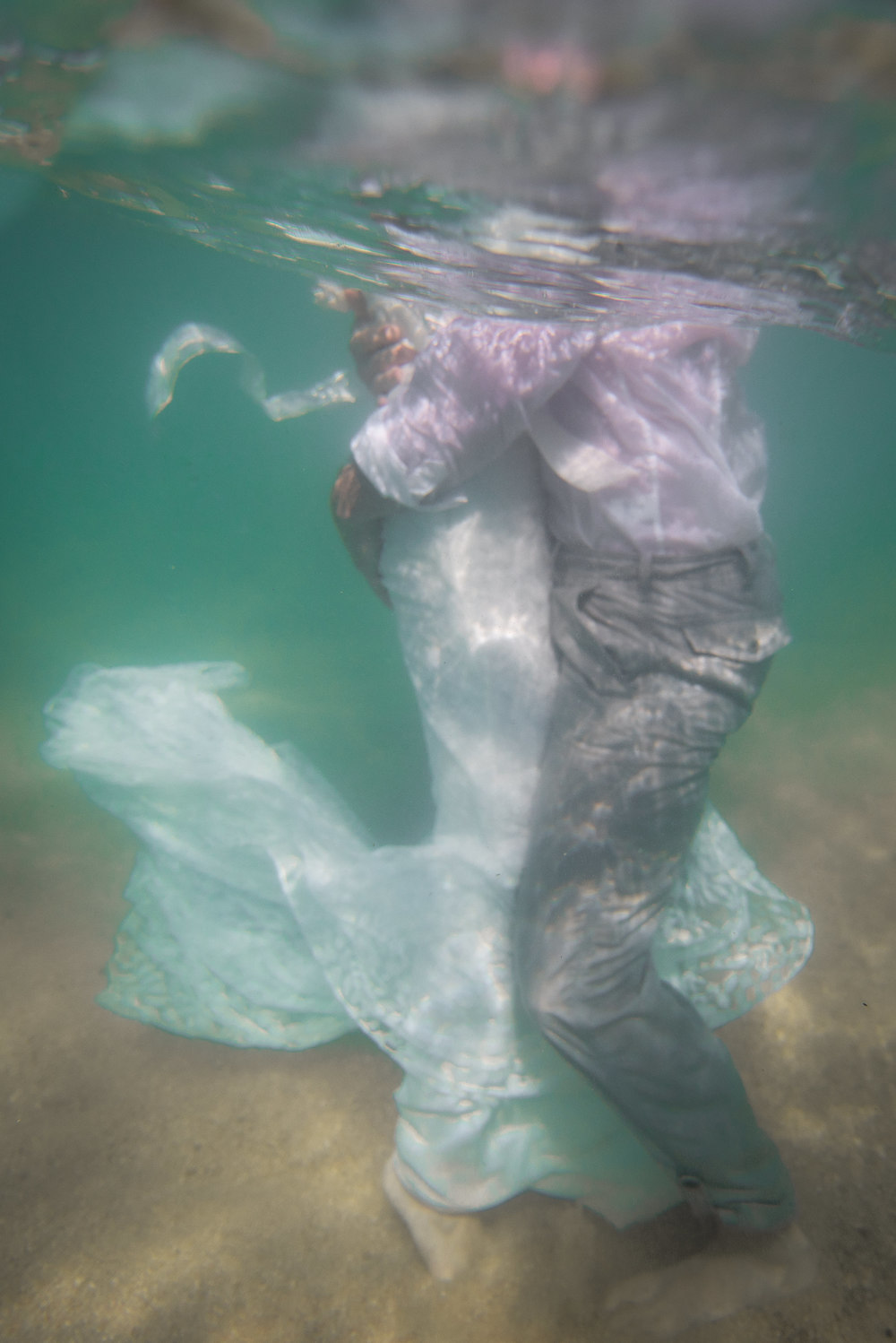 Underwater picture with bride and groom holding each other during their Trash The Dress session in Los Cabos