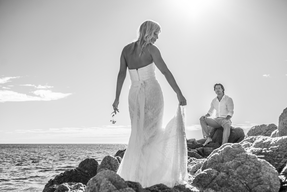 Los Cabos Bride is posing for her photo session, she is looking at her husband with the sea behind them