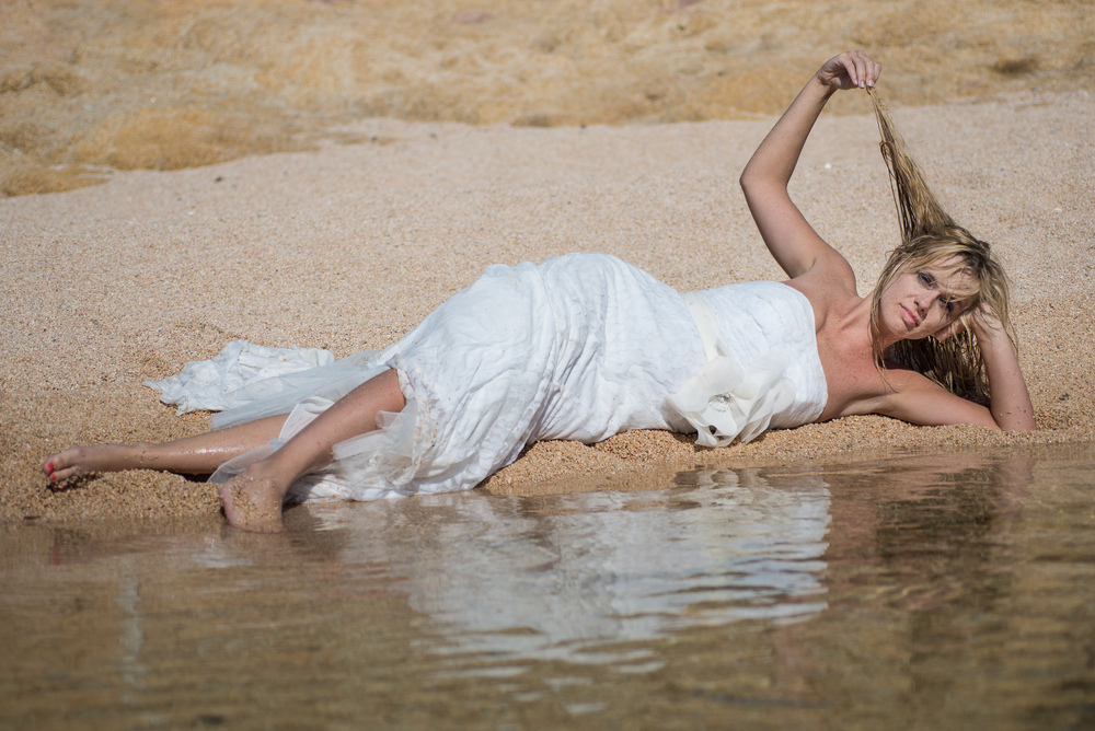 Bride is posing on a sandy beach in Cabo San Lucas during her trash the dress session