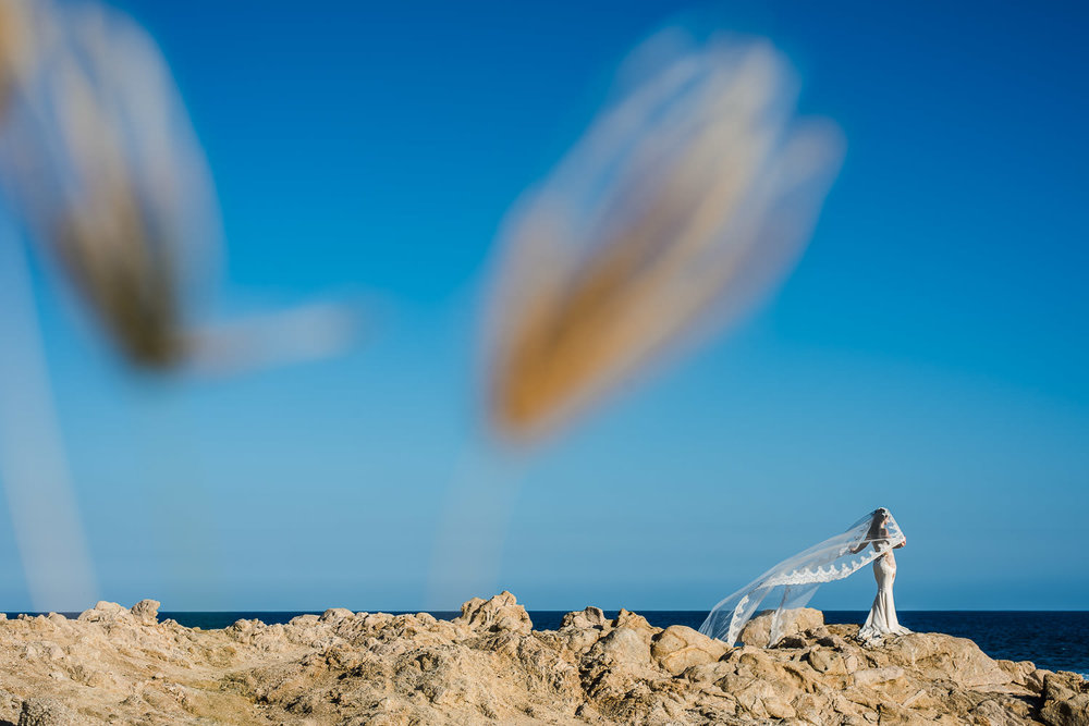 Bride with an amazing veil in fron of the Ocean