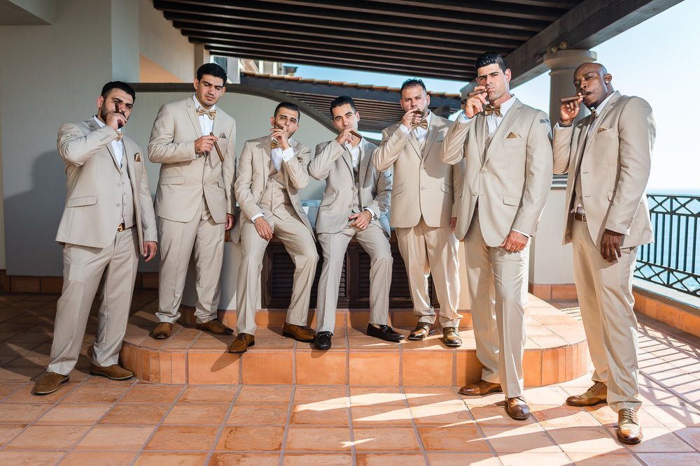 groom and groomsmen smooking cigars before the wedding