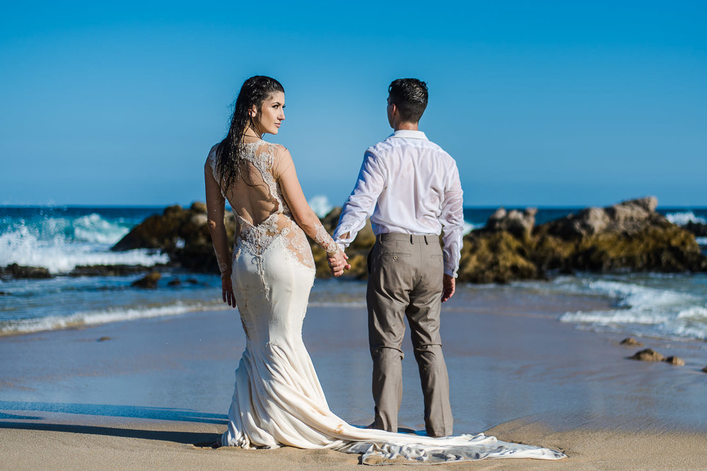 Bride and groom at beautiful Cabo beach during their trash the dress photo shooting with GVphotographer. Blue sky with an isolated beach, couple is wet with their wedding clothes. Gorgeous bride is looking to the camera meanqhile the groom looks to the ocean