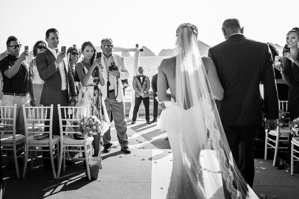 Bride walking down the aisle with her father surrounded with family and friends. Groom is waiting for her under the chuppah. Ocean and famous Cabo Arch is behind all the action