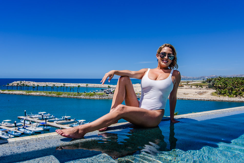 The lovely bride is sitting on the edge of the pool, she is looking at the camera and looking stunning. The Marina of San Jose del Cabo is right behind with all the boats, stunning views GVphotographer is an amazing destination wedding photographer based in Cabo San Lucas, Mexico