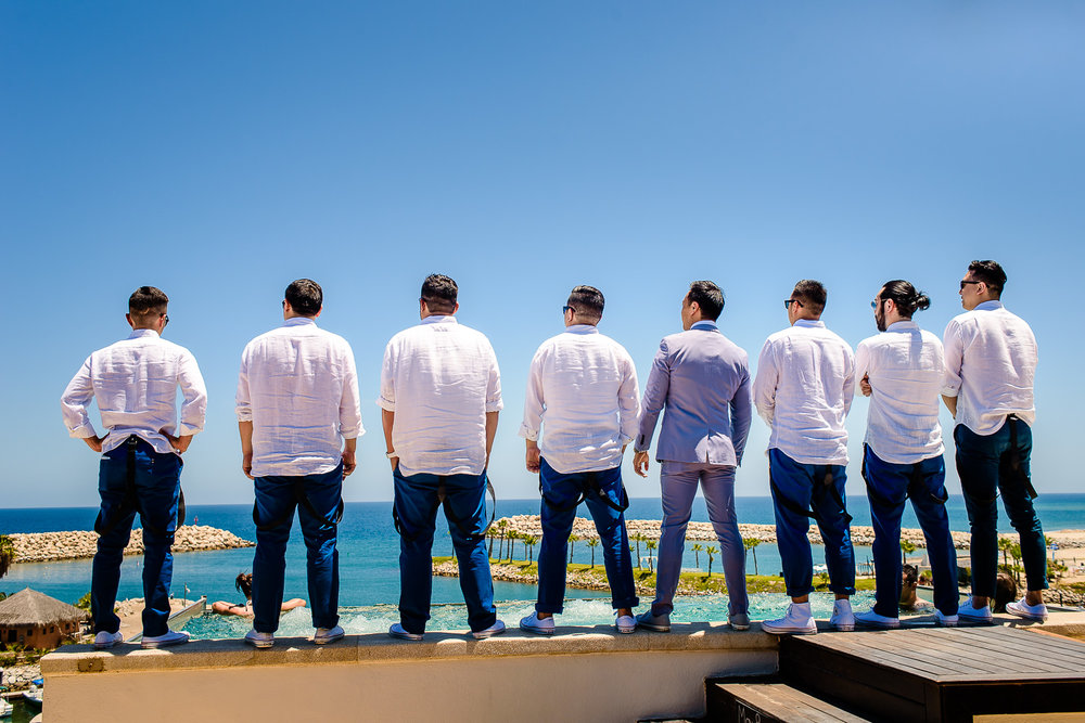 Groom with his friends are looking stunning wearing blue pants and white shirts, everybody is looking to the ocean destination wedding of the wonderful couple Cije and Jose at the beautiful El Ganzo, Mexico. GVphotographer is an amazing destination wedding photographer based in Cabo San Lucas, Mexico