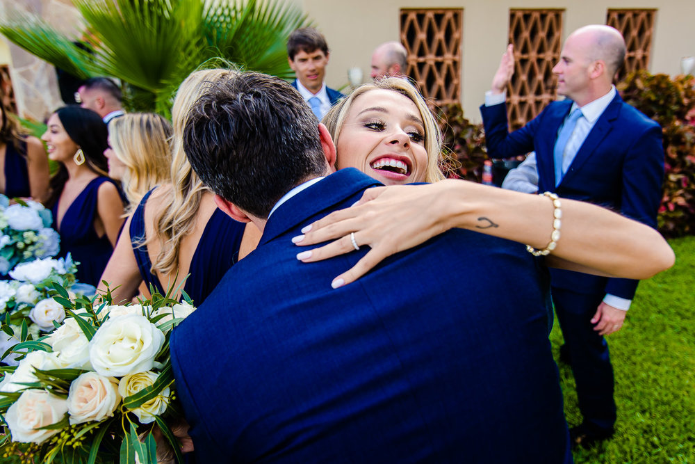 Bride hugging her friends right after the ceremony at Pueblo Bonito Sunset Beach Los Cabos. GVphotographer is an amazing Los Cabos destination wedding photographer