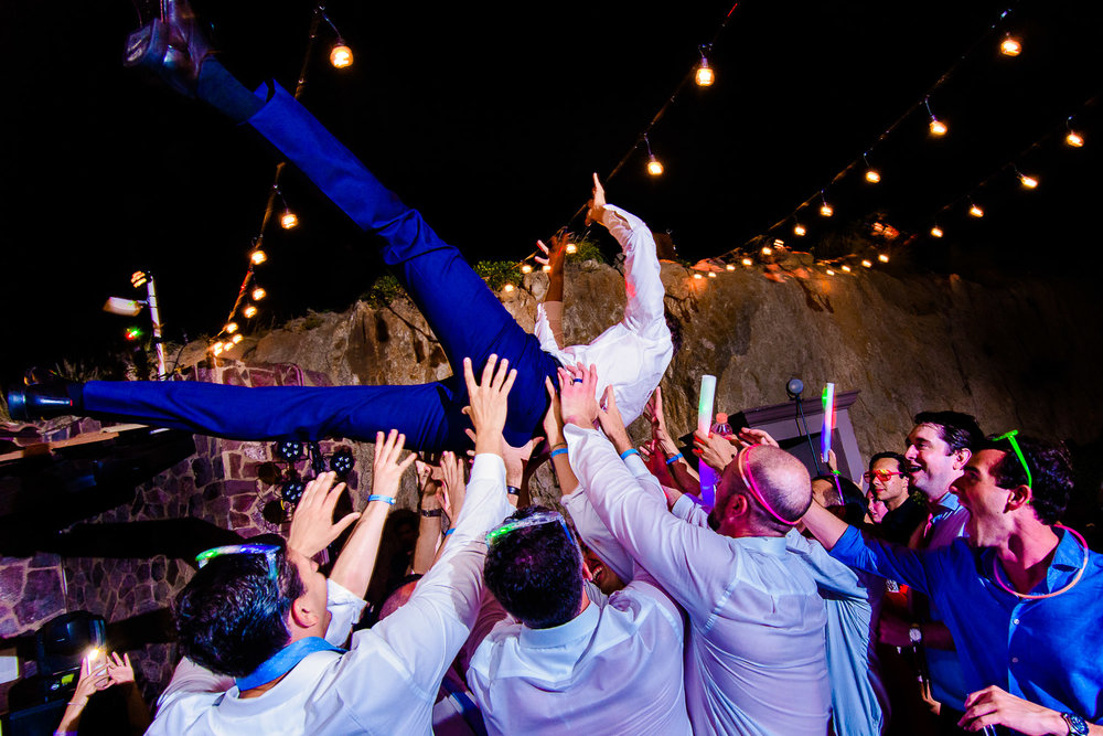The groom is enjoying his evening party dance while being held by his friends. Other guests are also dancing on the dance floor at the party- destination wedding of the wonderful couple Chelsea and Jay at the beautiful Pueblo Bonito Sunset Beach. GVphotographer is an amazing destination wedding photographer based in Cabo San Lucas, Mexico