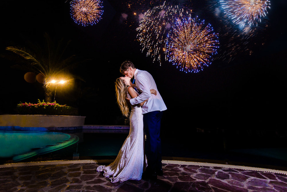 Bride and Groom kissing at their amazing fire works at the Pueblo Bonito Sunset Beach Skypool during Chelsea and Jay destination wedding. GVphotographer is an amazing destination wedding photographer based in Cabo San Lucas, Mexico