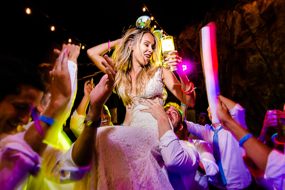 The bride is enjoying his evening party dance while being held by her friends. Other guests are also dancing on the dance floor at the party- destination wedding of the wonderful couple Chelsea and Jay at the beautiful Pueblo Bonito Sunset Beach. GVphotographer is an amazing destination wedding photographer based in Cabo San Lucas, Mexico